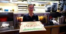 Friendly server with pizza at Chaser's Sports Bar & Grill in Niles