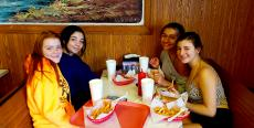 Friends enjoying french fries at Nick's Drive-In Restaurant in Chicago